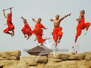 Shaolin-Monks jumping high with their weapons while training in the nature